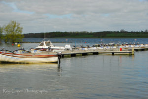 Fine art photography of waiting boats on a quiet lake. soft grey with green land behind.
